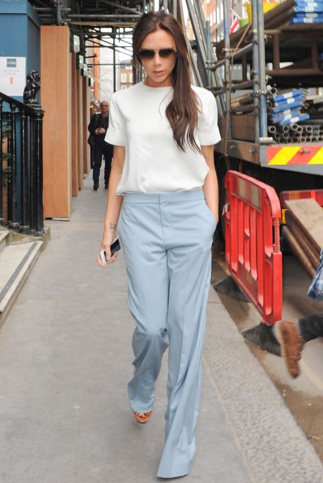 victoria beckham in white blouse and blue trousers