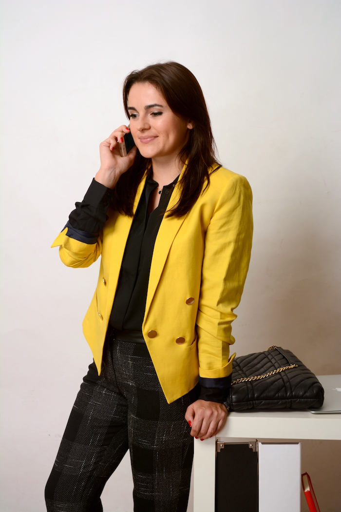 a beautiful woman wearing a yellow blazer to work
