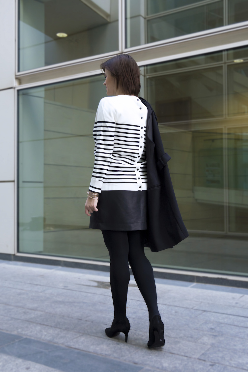woman wearing stripes sweater and leather skirt